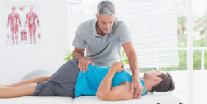 physical-therapist-stretching-lower-back-man